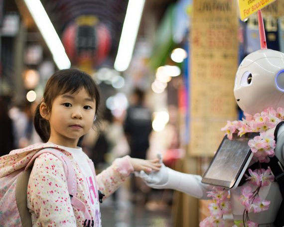 photo of girl laying left hand on white digital robot